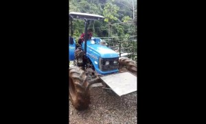 Honduran driver leaps to safety as tractor falls into raging river