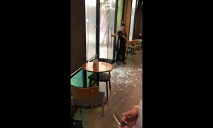 Coffee shop customers stunned as powerful storm smashes glass door in Thailand