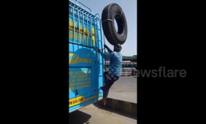 Man perfectly balances a huge tyre on his head as he climbs on the roof of a bus