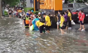 School children wade through water after flash floods in Bangkok
