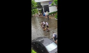 Ingenious schoolboys use three wooden chairs to cross flooded road in Thailand