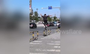 Daredevil unicyclist balances on roadside guardrails in China