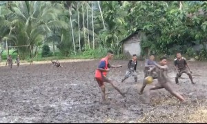 Indonesian teenagers attempt to play soccer in the thick mud of a rice field