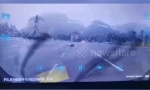 Lightning strikes ground inches away from scooter driver in China