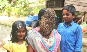 Indian woman covers her face with hundreds of bees to raise conservation awareness