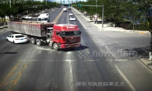 Truck driver narrowly avoids flattening car after changing directions quickly in China