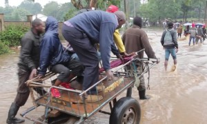 Pedestrians pay 10p to be taken across fast moving flood waters in Kenya