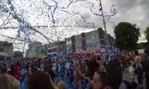Whacky performers blast UK high street with streamers and confetti