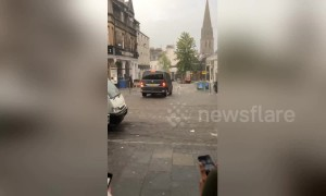 Bartenders chase after furniture being swept away by flooding in Scotland