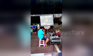 Man sets up outdoor karaoke stall under riverside bridge in China's Yichang