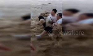 Pedestrians swept down road by flash flooding in China's Chongqing