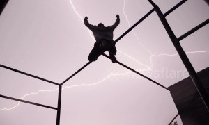 Free runner strikes a pose perfectly as bolts of lightning ignite the sky