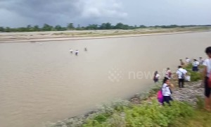 Children walk across a flooding river to attend school