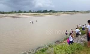 Children walk across a flooding river to attend school