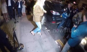 Pop star Rita Ora illuminated by press in London's Mayfair