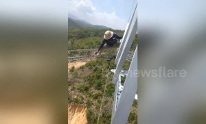 Vietnamese electrical workers do line repairs at terrifying heights