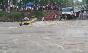 Passengers watch on as bus flips over in raging river in the Philippines