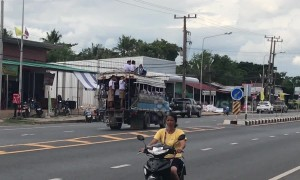 Reckless schoolboys climb onto roof of moving bus on busy road in Thailand