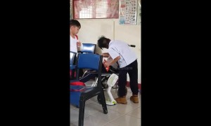 Touching moment two Filipino schoolboys help their classmate with cerebral palsy during break time