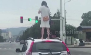 Angry woman climbs onto car roof on Chinese highway after 'arguing with husband'