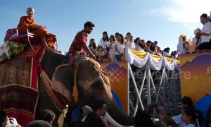 Thai monks ride elephants while receiving donations to mark the start of Buddhist Lent