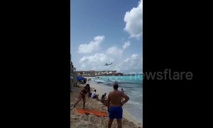 Beachgoers watch as planes fly low over Caribbean beach