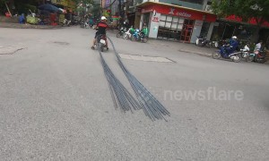 Motorbike stops traffic while dragging 6-metre long bundle of steel through crowded street