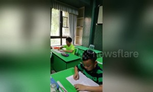 Chinese pupils balance plastic cups on heads while practising their handwriting