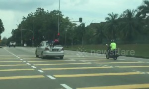 Reckless driver in Malaysia is caught jumping red light with two children clinging to roof