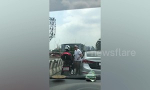 Shocking moment Filipino driver pokes motorcyclist in the eye and knocks him off before speeding away