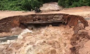 Shocking moment motorcyclists plunge into rapid floodwater after makeshift bridge collapses in Cambodia