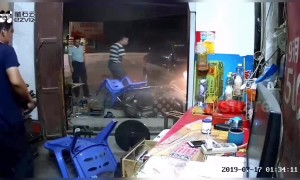 Car crashes into shop in southern China narrowly avoiding two men