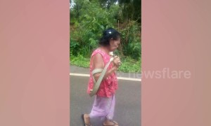 Bizarre moment grandmother, 75, carries live cobra down the road 'while in a trance'