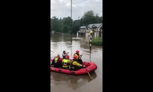 Emergency services use lifeboats to rescue stranded residents from flooding in Bramhall, Greater Manchester