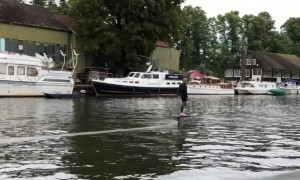 Man on a hover surfboard zooms along the River Thames