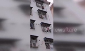 Firefighters rescue boy hanging from fourth-floor window in central China