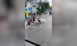 Pedestrians wade through flood water in the Philippines