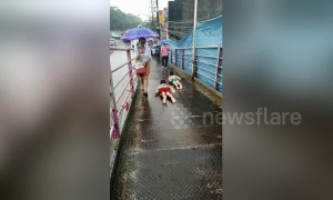 Children use pedestrian bridge as water slide during Philippines rain storm