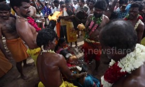 Smashing it! Devotees line up to have coconuts broken on their heads in traditional Indian festival