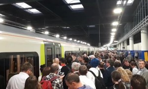 Long line of passengers wait to board train at Euston station in London