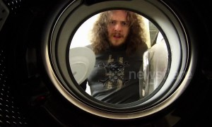 Man loads washing machine with dirty dishes