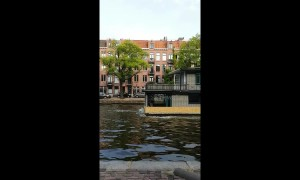 Moving house in Amsterdam: Tugboats pull two-storey houseboat along canal