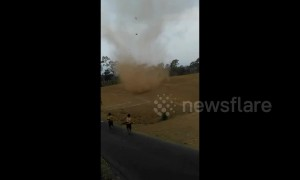 Fearless kids run into massive dust devil in Indonesia