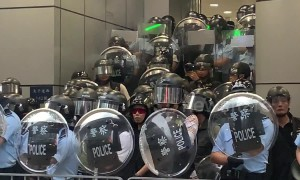 Hong Kong riot police violently shove journalist