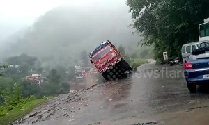 Pedestrians watch on as truck topples off cliff during landslide in northern India