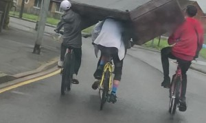 Squad of Cyclists Carry a Couch