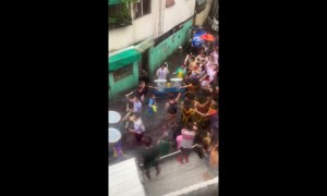 Carnival in Philippines crosses road flooded by Storm Bailu