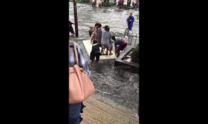 Women float on polystyrene board across road flooded by Storm Bailu