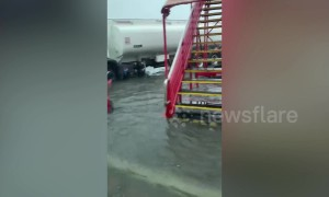 Airport bus drives passengers across flooded tarmac after tropical storm