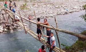 Villagers waiting six years for bridge to be finished make their own from bamboo